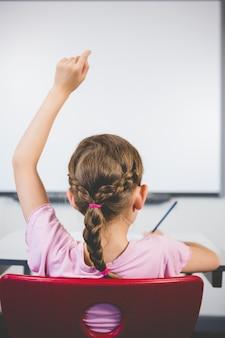 Vista traseira da colegial, levantando a mão na sala de aula