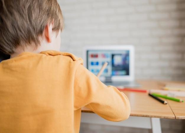 Vista traseira da criança aprendendo com o laptop em casa
