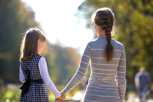 Vista traseira da criança menina e mãe de mãos dadas