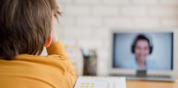 Vista traseira da criança sendo tutelada em casa através da aula on-line