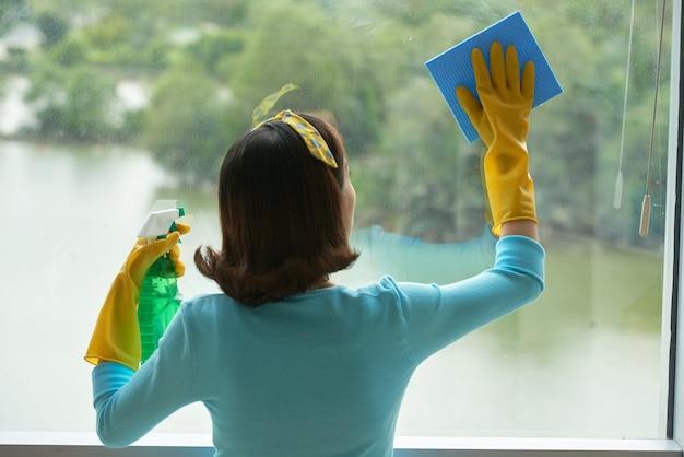 Vista traseira da empregada pin-up, limpeza de janela panorâmica com limpador de spray e esponja