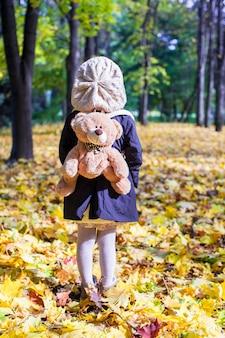 Vista traseira da encantadora menina com uma mochila-urso para trás na floresta ensolarada de outono