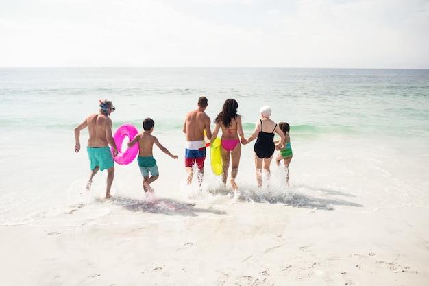 Vista traseira da família correndo em direção ao mar
