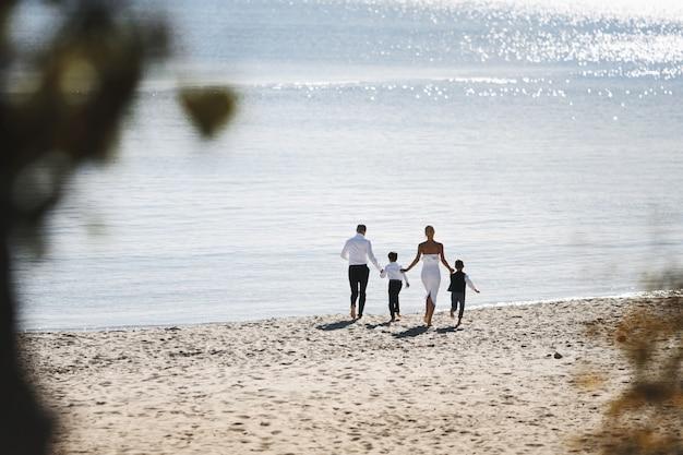 Vista traseira da família em execução na praia em dia ensolarado perto do mar, vestida com roupas da moda