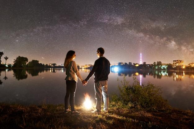 Vista traseira da família jovem - homem e mulher em pé na margem do lago perto da fogueira, de mãos dadas, apreciando a maravilhosa vista do céu noturno cheio de estrelas e via láctea acima da água parada e da cidade luminosa