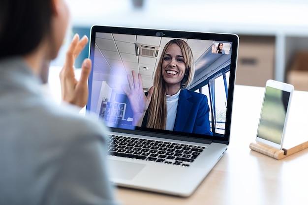 Vista traseira da funcionária acenando e falando em videochamada com seu colega no briefing on-line com o laptop em casa.