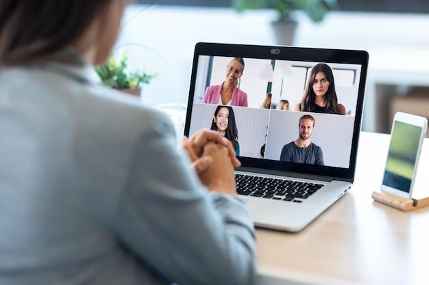 Vista traseira da funcionária falando em videochamada com diversos colegas em briefing online com laptop em casa.