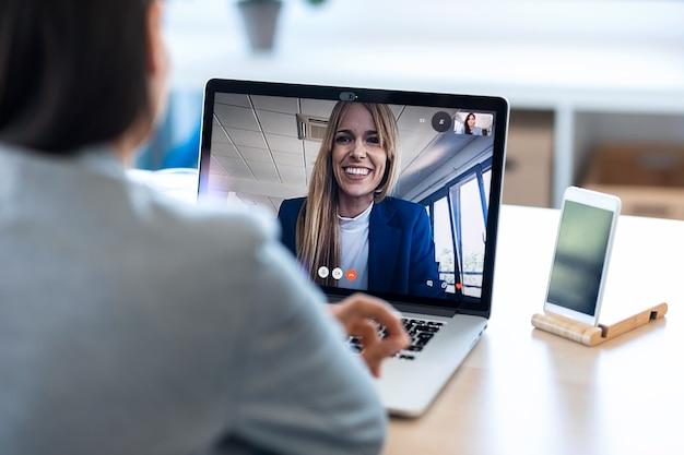 Vista traseira da funcionária falando em videochamada com seu colega no briefing on-line com o laptop em casa.