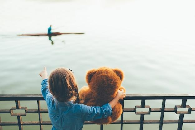 Vista traseira da garota abraçando um fofo urso de pelúcia mostrando para uma canoa