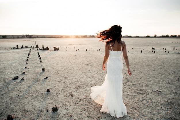 Vista traseira da garota caucasiana em vestido longo branco sem mangas à noite na área arenosa