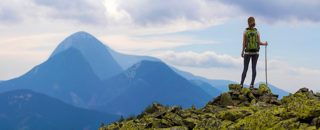 Vista traseira da garota jovem turista magro mochileiros com vara em pé na parte superior rochosa contra o céu azul brilhante da manhã, apreciando o panorama de montanhas nevoentas. conceito de turismo, viagens e escalada.