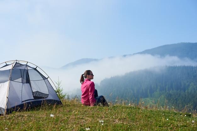 Vista traseira da garota jovem turista sentado na grama verde do vale de florescência