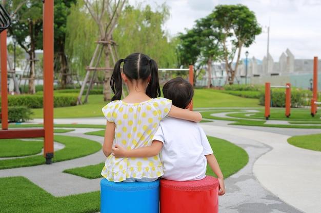 Vista traseira da irmã mais velha abraça o irmão mais novo pelo pescoço, ombros sentado no playground no jardim com vista ao ar livre no parque.