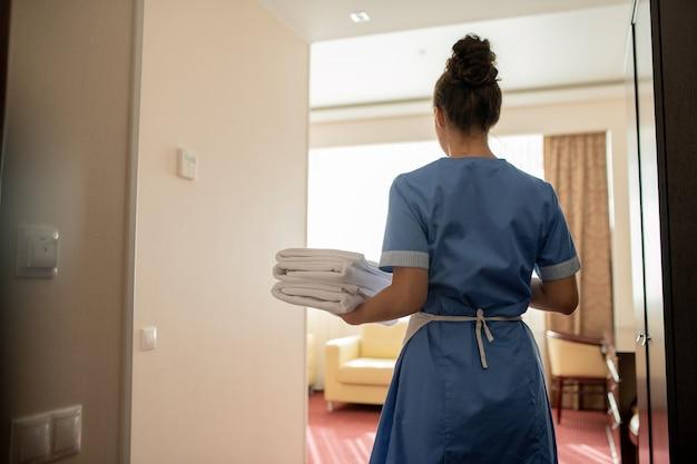 Vista traseira da jovem camareira morena de uniforme carregando uma pilha de toalhas brancas para os hóspedes ao entrar em um dos quartos