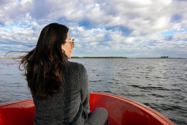 Vista traseira da jovem desfrutar no barco e olhando para a frente em lagoa