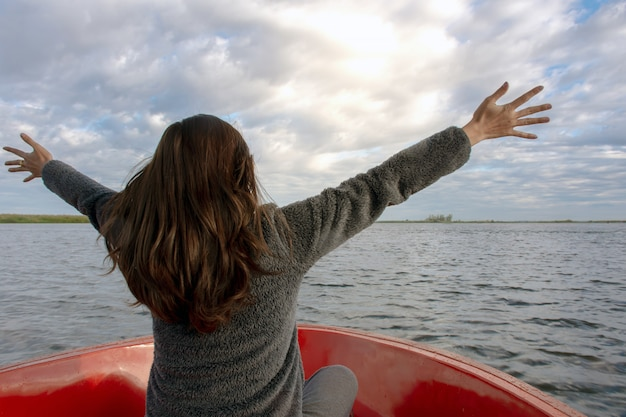 Vista traseira da jovem estendendo os braços e desfrutar no barco e olhando para a frente em lagoa