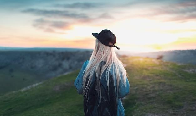 Vista traseira da jovem loira com boné preto e mochila, caminhando no pico das colinas. plano de fundo do pôr do sol.