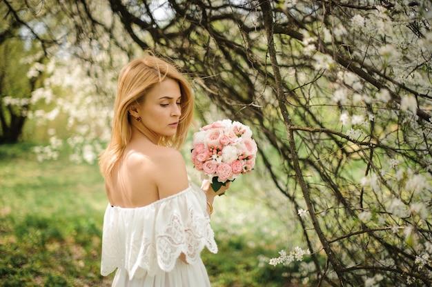 Vista traseira da jovem loira em um vestido branco com buquê perto da árvore de cereja em flor