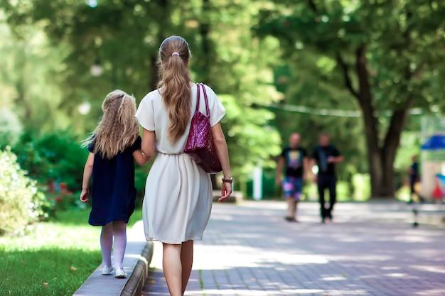 Vista traseira da jovem mãe andando com a filha menina em