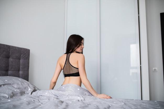 Vista traseira da jovem mulher exercitando em casa, sentado na cama, esticando.