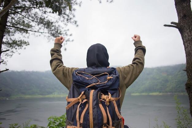 Vista traseira da jovem mulher muçulmana asiática com as mãos para o alto em pé na falésia sobre o lago. conceito de viagens, conceitos de vencedor, liberdade,