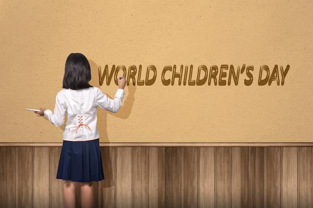 Vista traseira da linda garota asiática pintando um texto do dia mundial das crianças na parede. dia mundial da criança