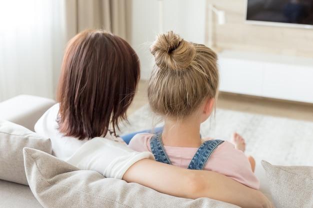 Vista traseira da mãe e filha sentada no sofá em sua casa e assistindo tv, conceito de tempo para a família