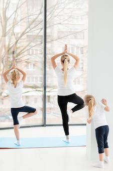 Vista traseira da mãe em pose de ioga com filhas