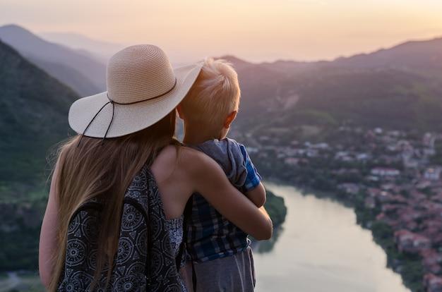 Vista traseira da mãe segurando o filho jovem na bela paisagem. viajar com o conceito de crianças
