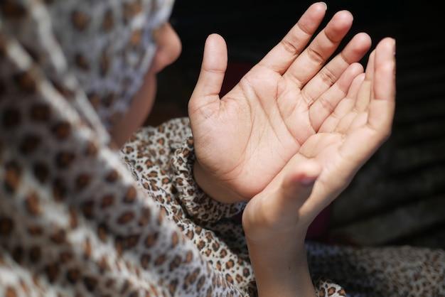Vista traseira da mão de uma mulher muçulmana orando à noite