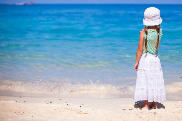 Vista traseira da menina adorável em uma praia exótica