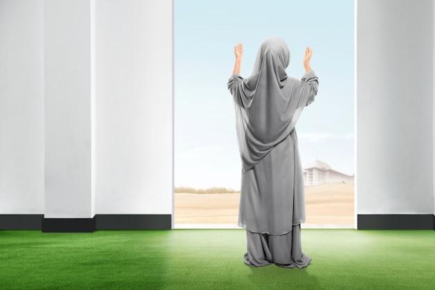 Vista traseira da menina asiática no véu de pé no tapete levantar a mão e olhando o céu de dentro da sala
