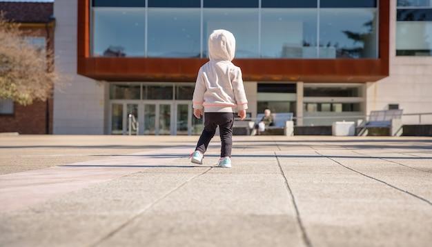 Vista traseira da menina com tênis e moletom em pé em uma praça da cidade em um dia ensolarado