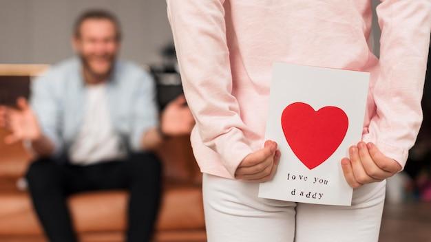 Vista traseira da menina dando um cartão para o pai no dia dos pais