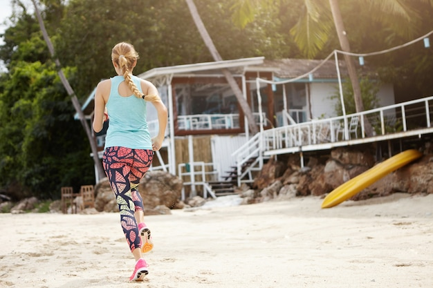 Vista traseira da menina desportiva com longa trança durante o exercício de corrida ao ar livre. atleta de mulher loira com leggings coloridas correndo na praia pela manhã, preparando-se para uma maratona séria.