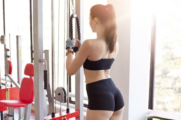 Vista traseira da menina desportiva magro, vestindo roupas esportivas, posando para trás enquanto treinava na estação de fitness, fazendo exercícios para tríceps e costas, levar estilo de vida saudável.