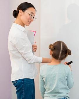 Vista traseira da menina escrevendo em um quadro branco ao lado de seu professor