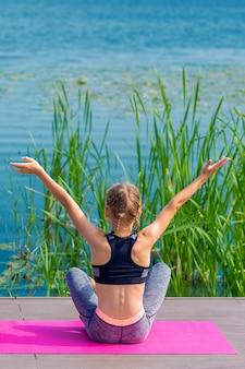 Vista traseira da menina está fazendo exercícios de ioga
