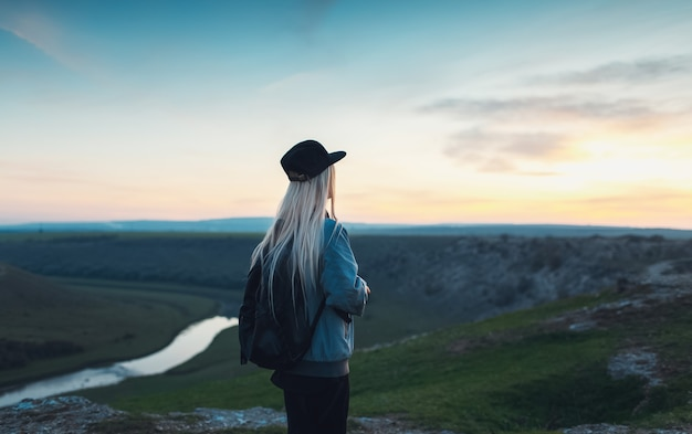 Vista traseira da menina loira com mochila preta e boné. jovem viajante olhando o pôr do sol nas colinas.