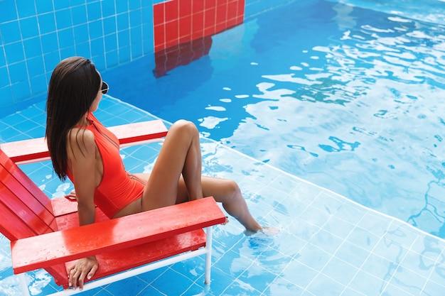 Vista traseira da morena em um maiô vermelho, sente-se na cadeira de salva-vidas na piscina, mergulhando os pés à beira da piscina.