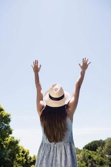 Vista traseira da morena levantando as mãos à beira da piscina