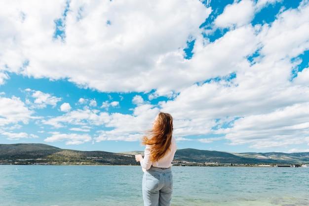 Vista traseira da mulher, apreciando a vista do oceano com montanhas
