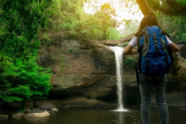 Vista traseira da mulher asiática com mochila, observando a pequena cachoeira na selva.