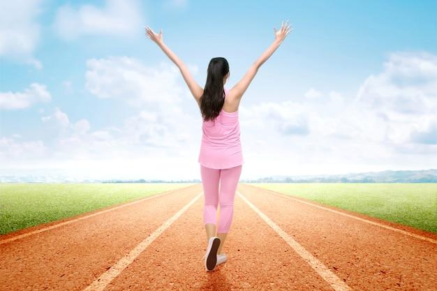 Vista traseira da mulher asiática corredor com expressão animada depois de uma corrida na pista de corrida