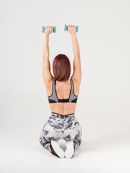 Vista traseira da mulher atlética segurando pesos