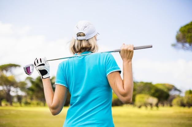 Vista traseira da mulher carregando taco de golfe