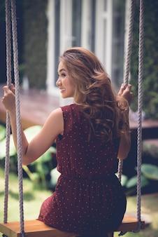 Vista traseira da mulher com cabelos ondulados bonitos balançando no jardim da frente