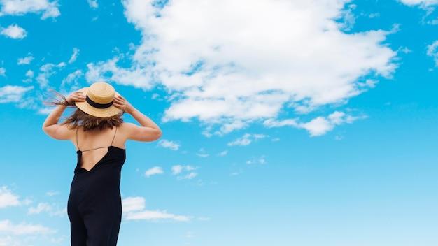 Vista traseira da mulher com chapéu e céu com nuvens