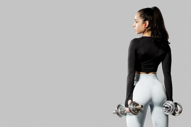 Vista traseira da mulher com halteres e cópia espaço