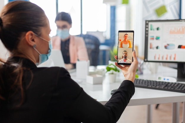 Vista traseira da mulher com máscara facial falando durante a videochamada de negócios, mantendo o distanciamento social no local de trabalho, precaução de segurança contra a infecção com a gripe covid19 no local de trabalho.